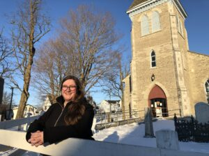 Image of Jessica leaning on the fence at Macaulay Heritage park on a sunny winter day. A historic church and graveyard in the background.