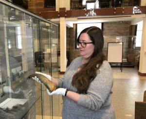 Jessica Chase holds an artefact wearing white gloves inside the Macaulay Church museum.