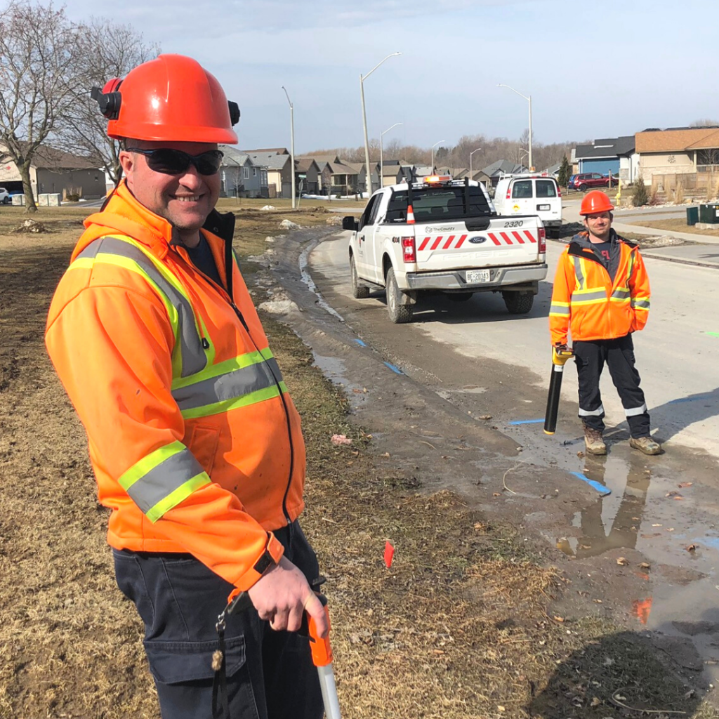 Jason Young stands in the foreground wearing orange safety jacket and hat. Darius in the background holding a paintin tool, in front of a white pickup truck.